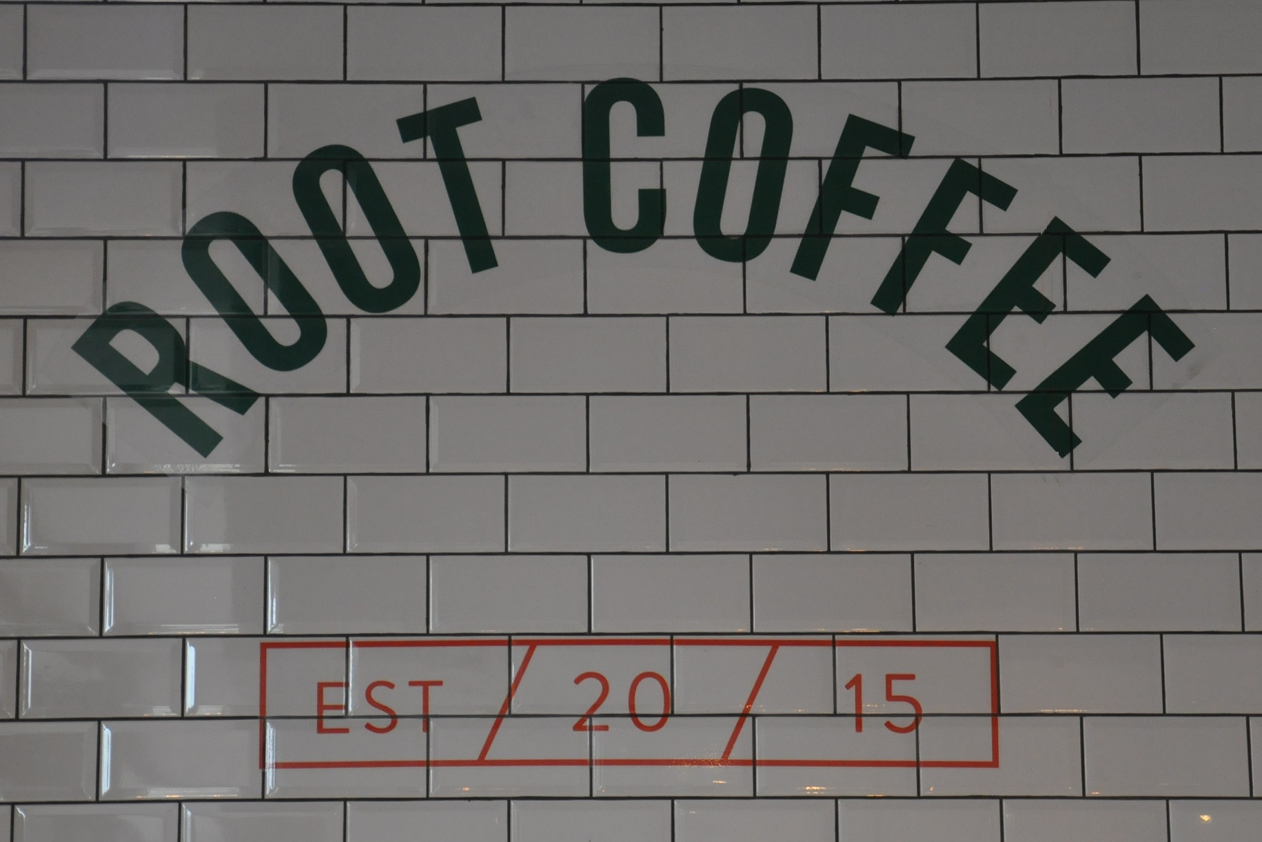 "The words ""Root Coffee"" written in an arch in black capitals on white, tiled wall. ""EST / 20 / 15"" is written in red in a box below."