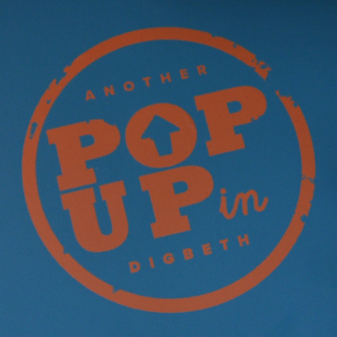 """The words """"Another Pop Up in Digbeth"""" written in orange inside an orange circle on a blue background. POP UP is in capitals, with the space in the O replaced by an upwards-pointing arrow."""