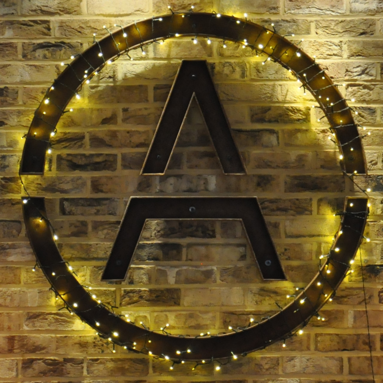 The letter A in a circle, mounted on a exposed brick wall. The circle is wrapped in fairy lights.