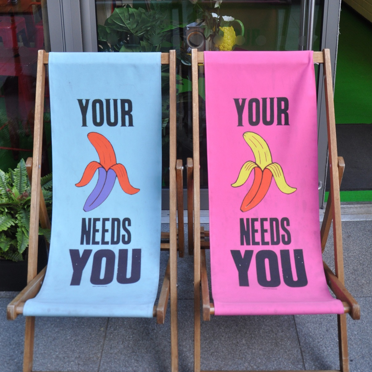 "A pair of Beany Green deckchairs, blue on the left, pink on the right. Each shows a half-peeled banana with the word ""YOUR"" above the image, and ""NEEDS YOU"" underneath."