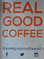 "The words ""REAL GOOD COFFEE"" in orange on white-painted brick wall. At the bottom, in blue, is Compass Coffee's social media details."