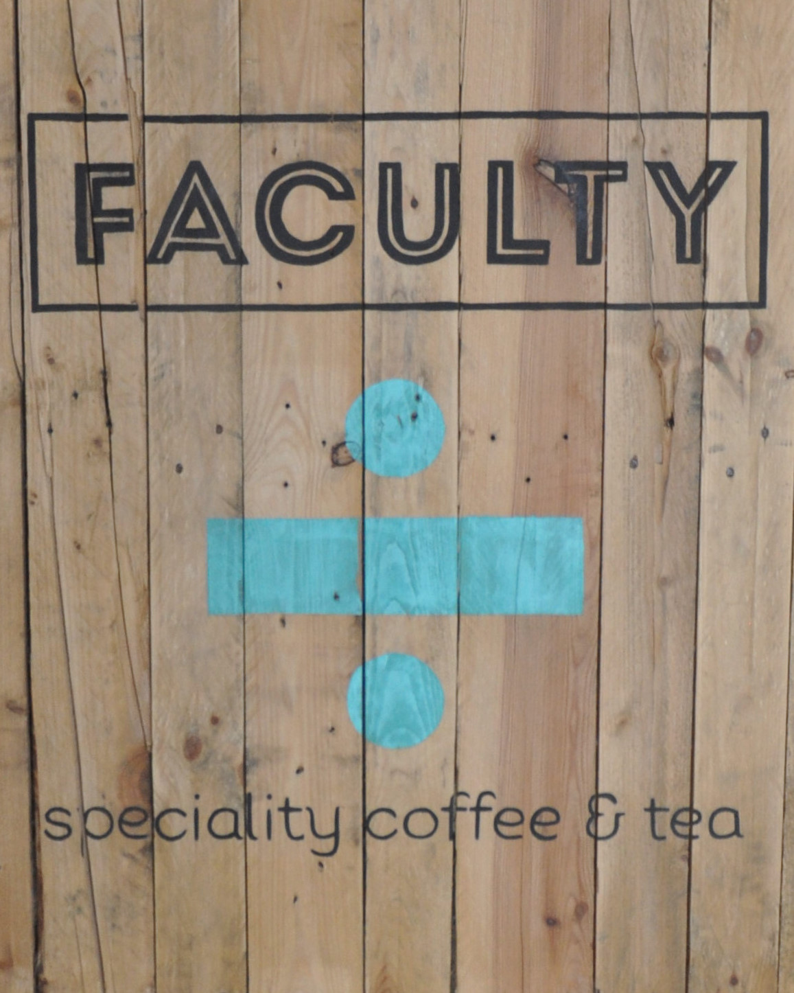 """A series of vertical wooden boards with the words """"Faculty"""" and """"speciality coffee & tea"""" written horizontally across them, with a blue division sign in the centre."""