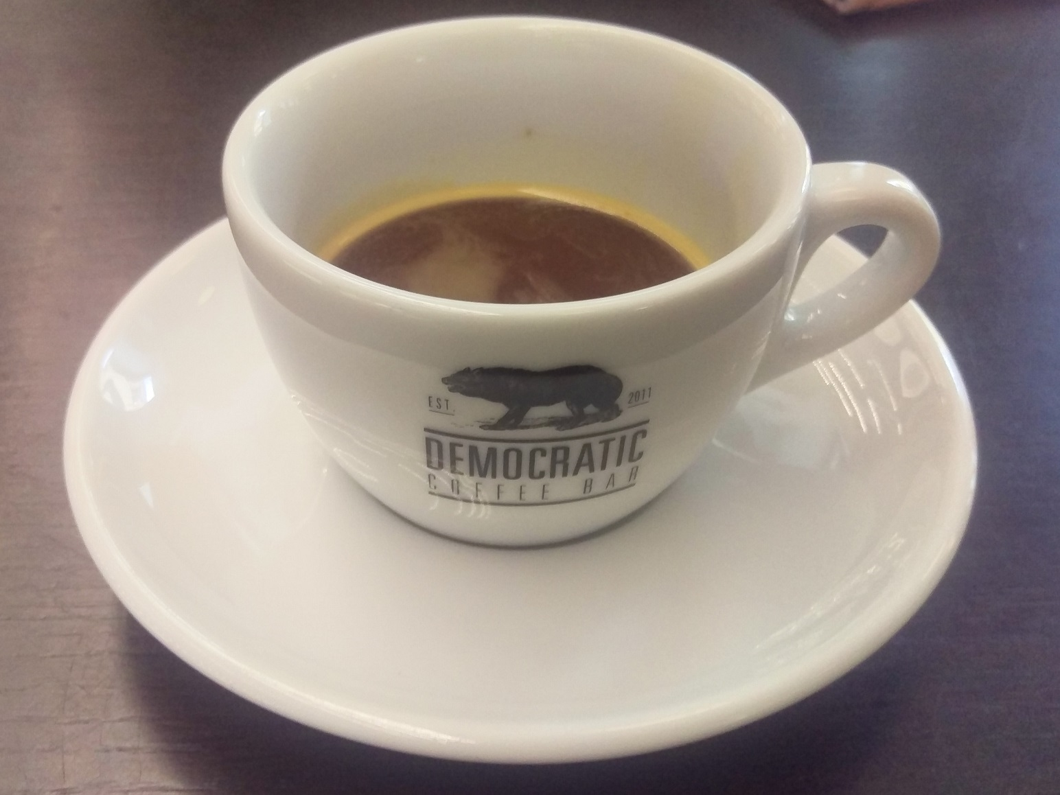 A white cup, with the Democratic Coffee logo, an etching of a wolf from a manuscript in the adjacent library
