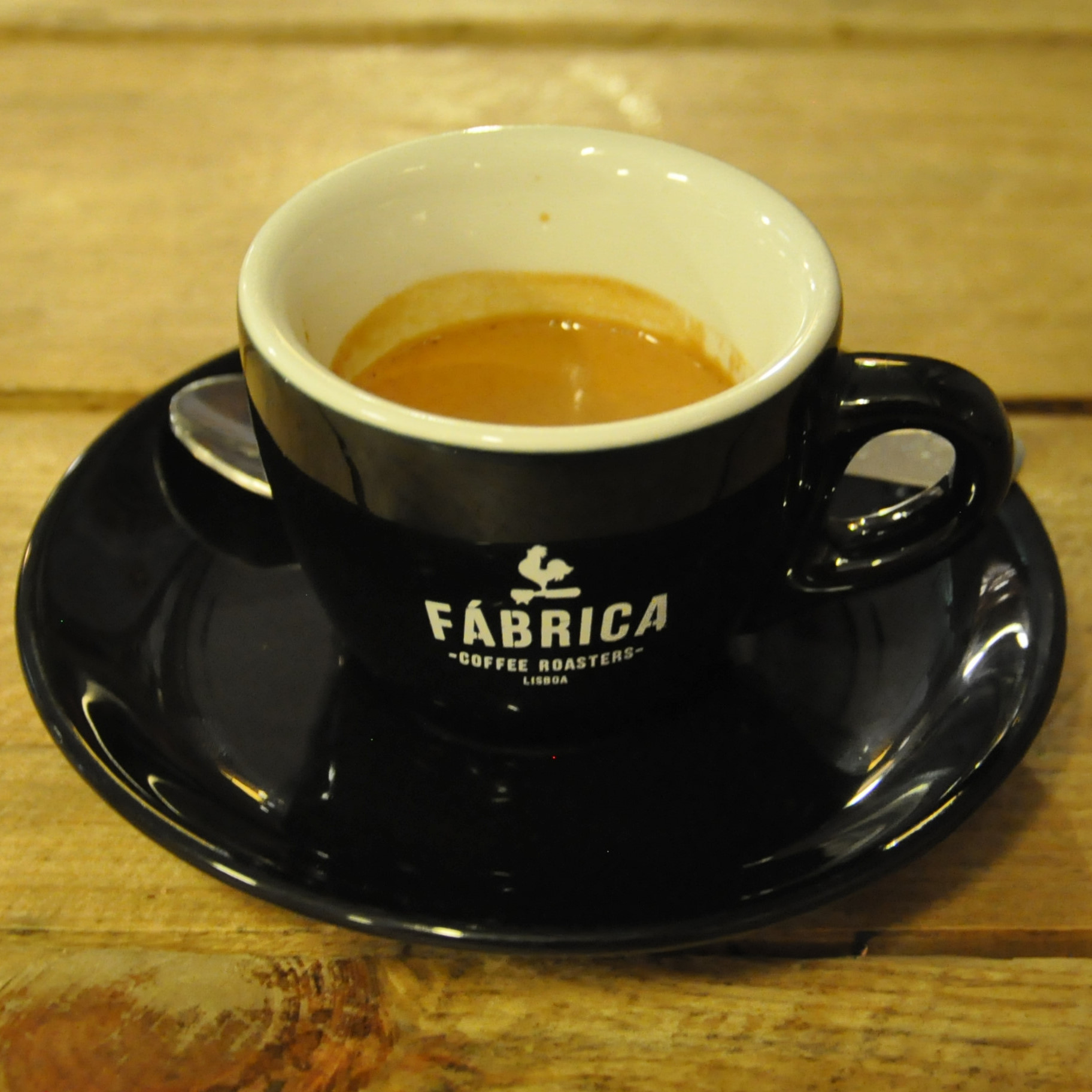 "An espresso in a classic black cup, with white interior, on a black saucer. The words ""Fábrica Coffee Roasters Lisboa"" are written in white on the side of the cup."