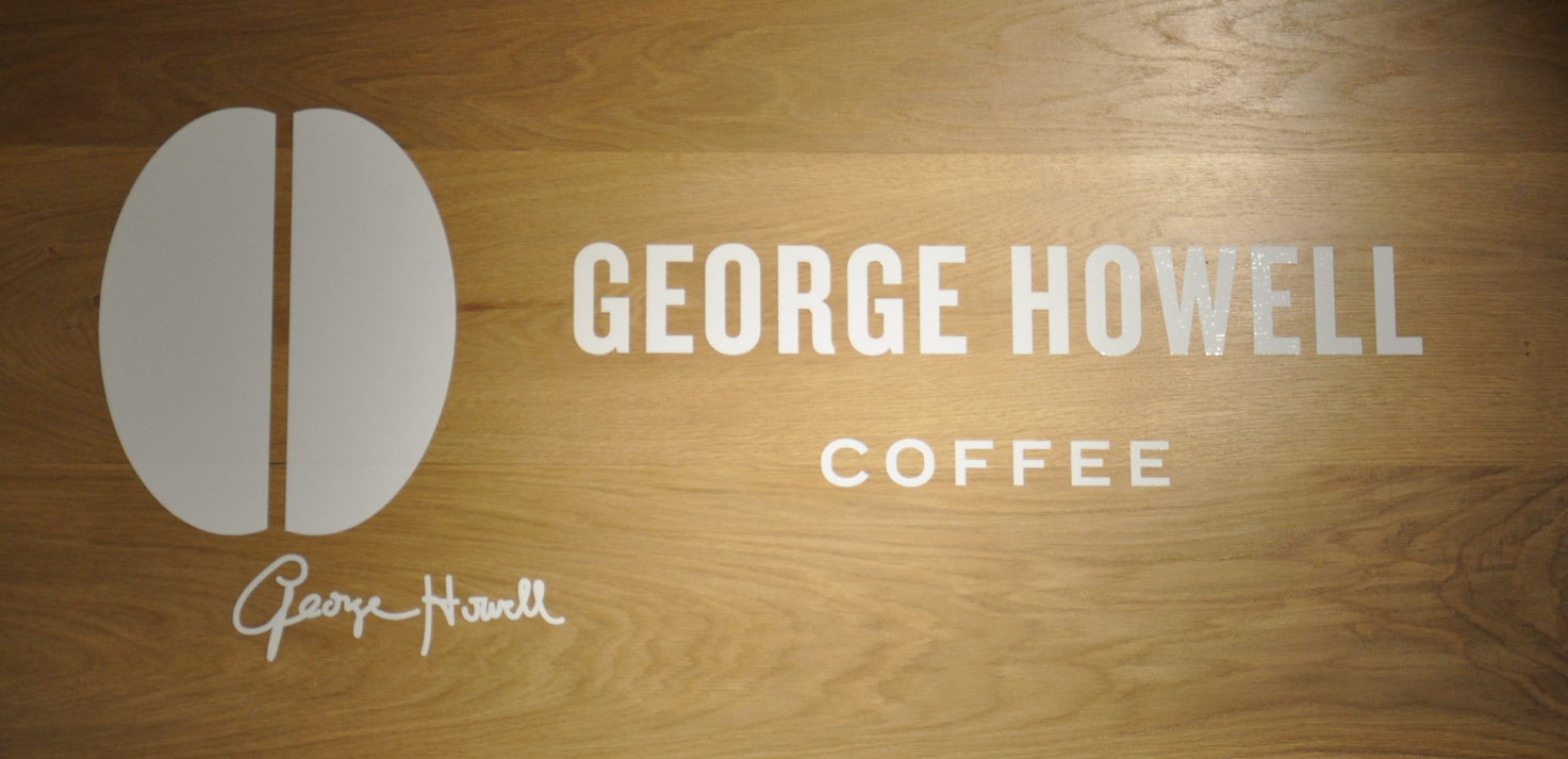 """George Howell Coffee"" written in white on a wooden board, next to a silhouette of a coffee bean with George Howell's signature beneath it."
