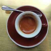 "An espresso, seen directly from above, the brown of the crema matching that of the saucer and contrasting with the white interior of the cup. The word ""Stumptown"" is written in script on the top rim of the cup."