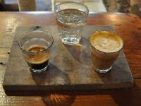 A one and one (otherwise known as a split shot), beautifully presented on a wooden tray with a glass of soda water at Cartel Coffee Lab in Tempe, Arizona.
