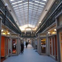 The soaring, vaulted glass ceiling of the central aisle of the Arcade Providence, home of New Harvest Coffee & Spirits.