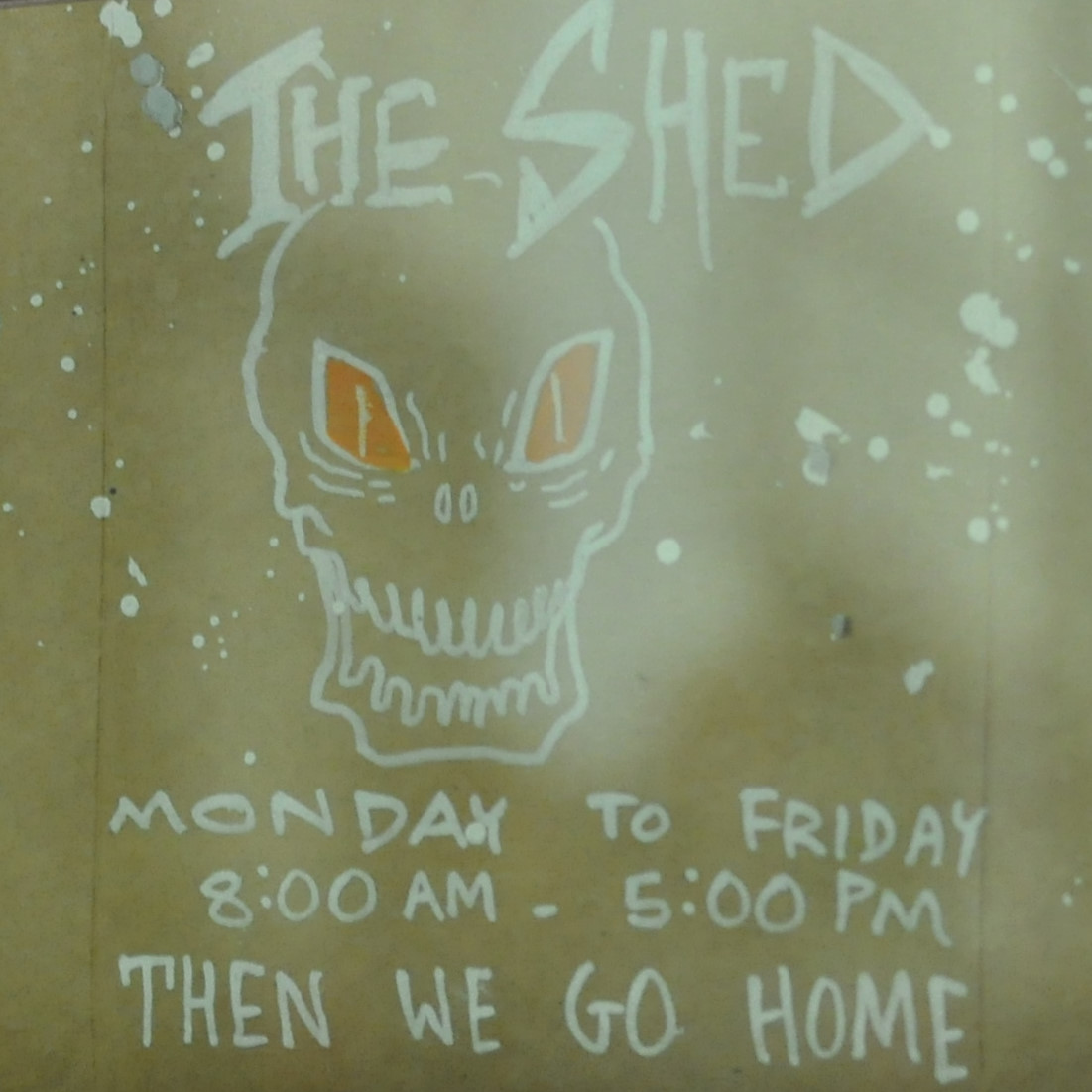 The opening times, and a grinning skull, taken from the door of Taylor St Baristas, The Shed.