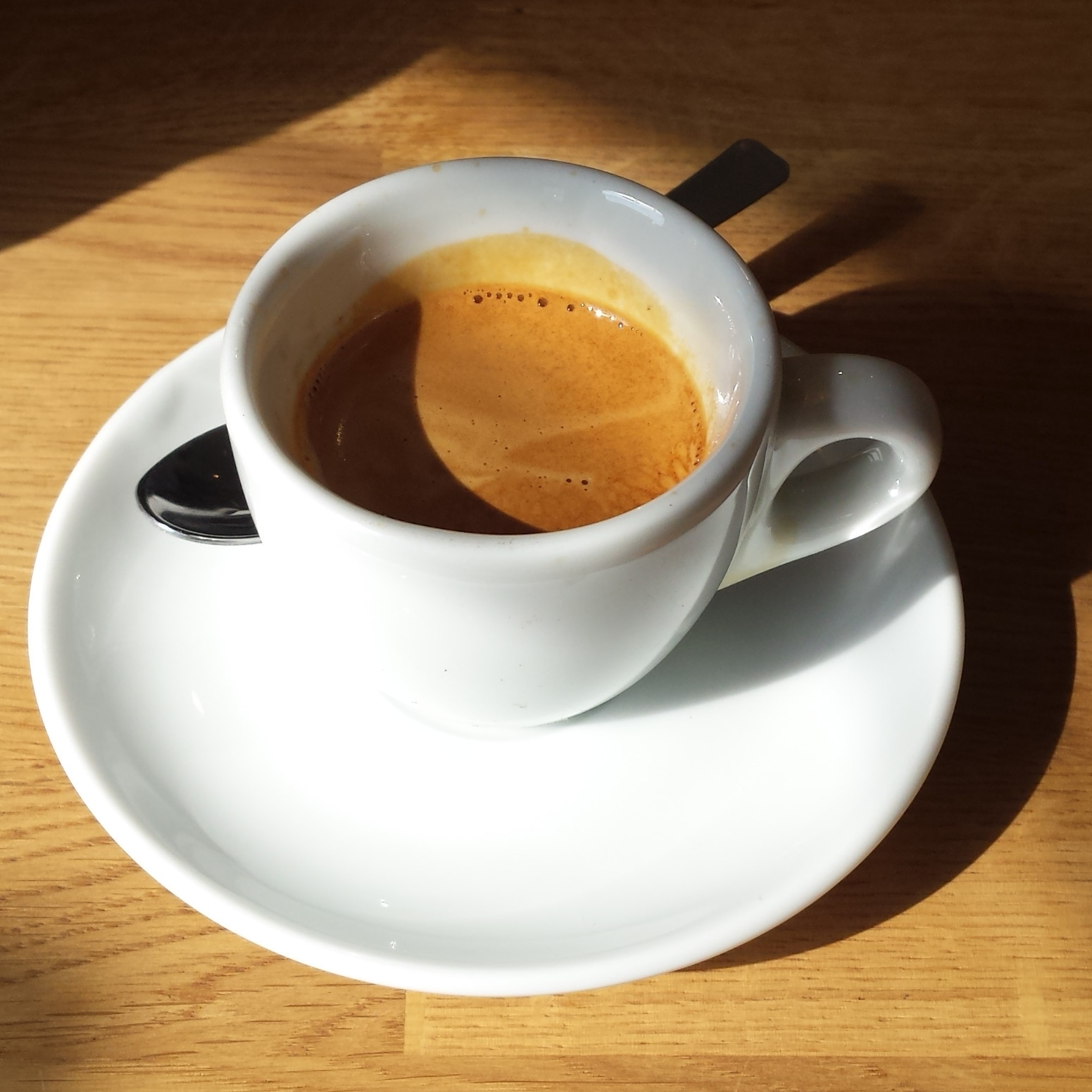 A lovely espresso in a classic white cup being enjoyed in the sun at Canopy Coffee, Guildford.