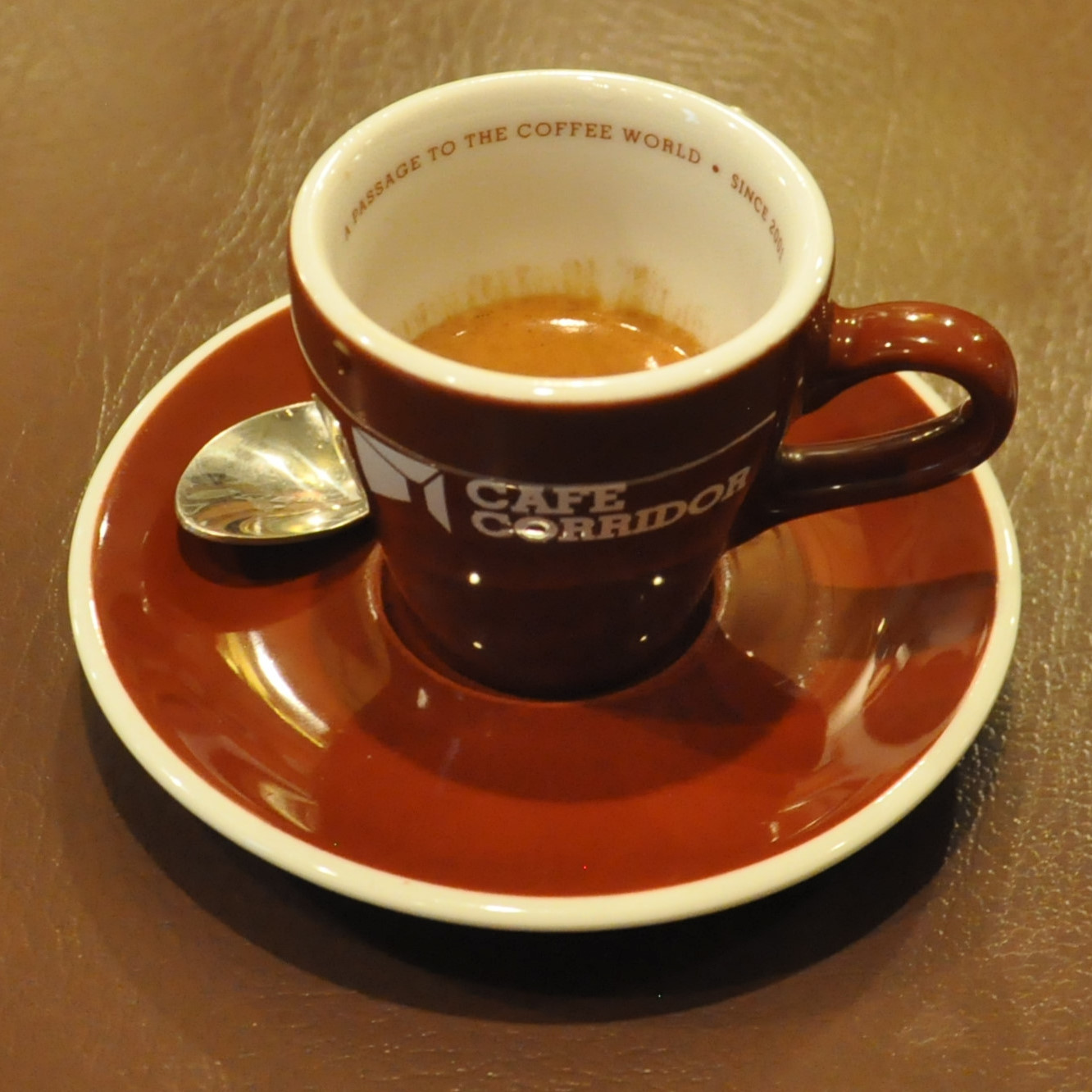 A single-origin Colombian espresso in a branded cup from Cafe Corridor in Hong Kong with 'A passage to the coffee world since 2001' written on the inside rim.