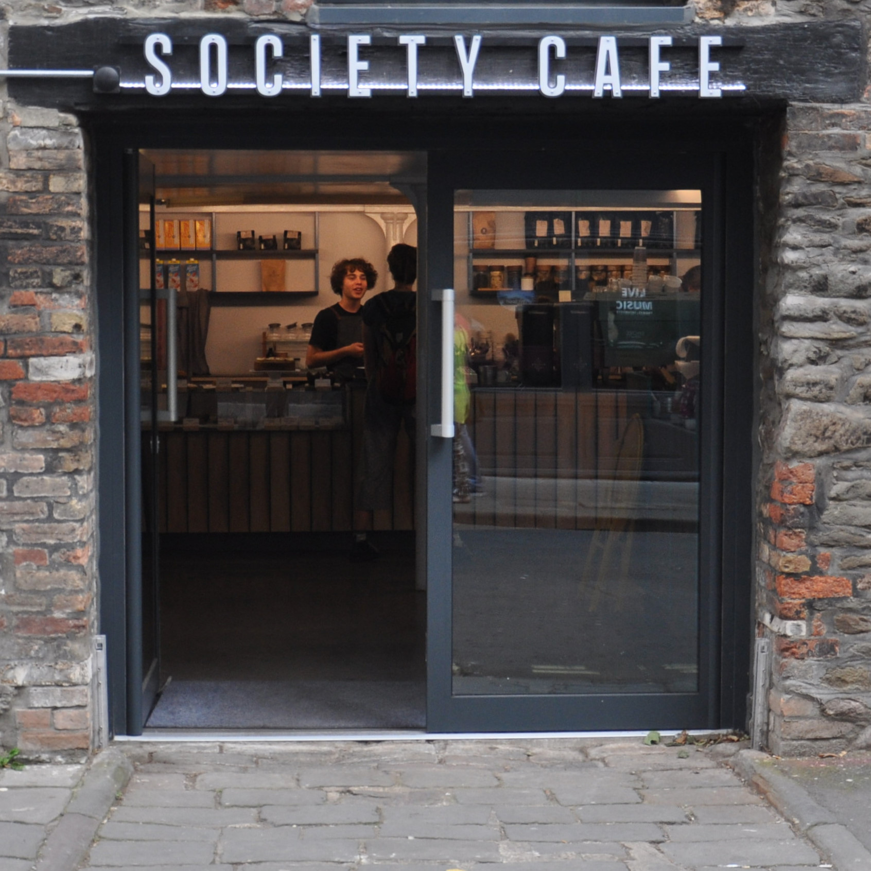 The main entrance to Society Cafe in Bristol, a pair of glass double-doors opening out onto Farr's Lane, with the counter directly ahead.