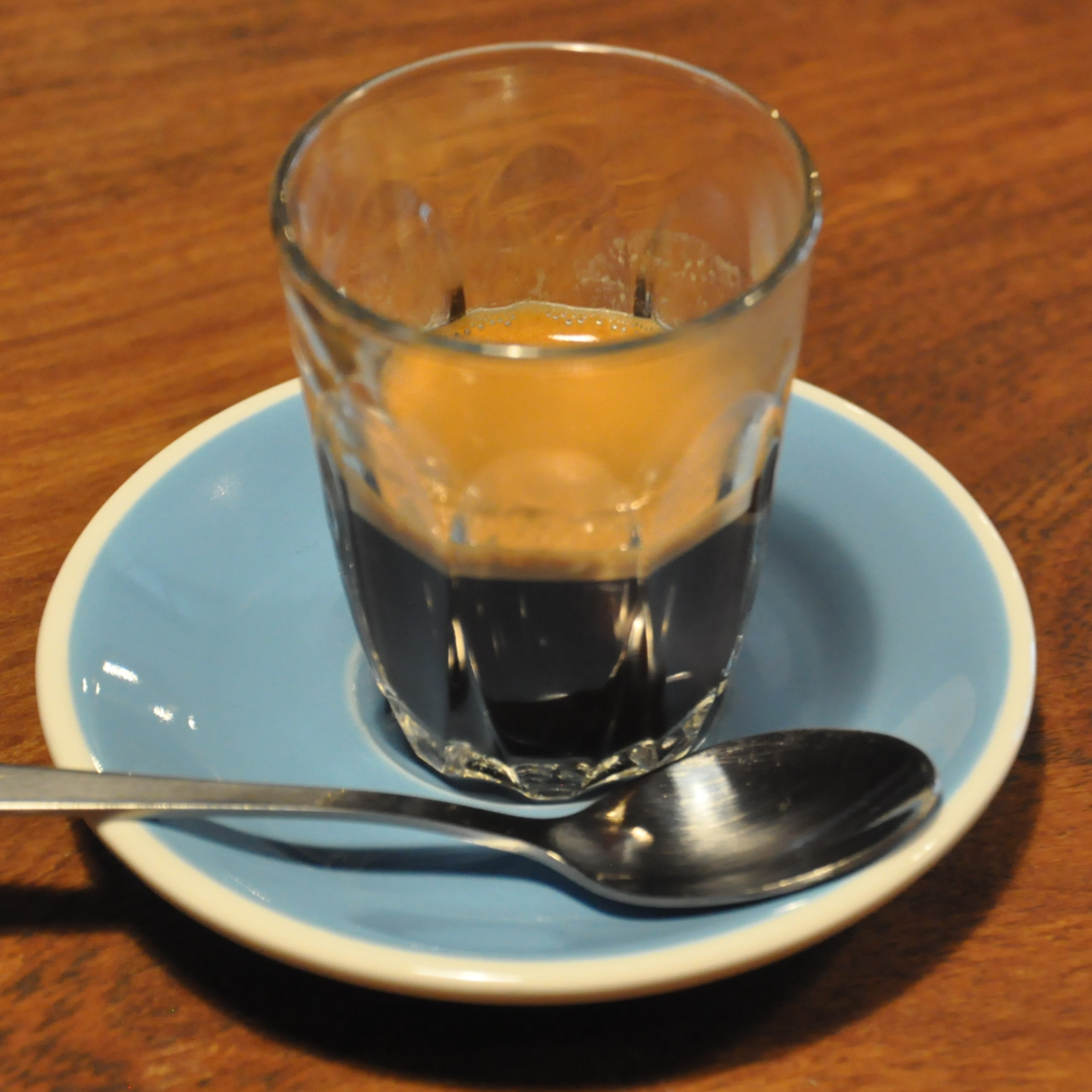 An espresso in a glass, served on a blue saucer at March Coffee, Exeter.