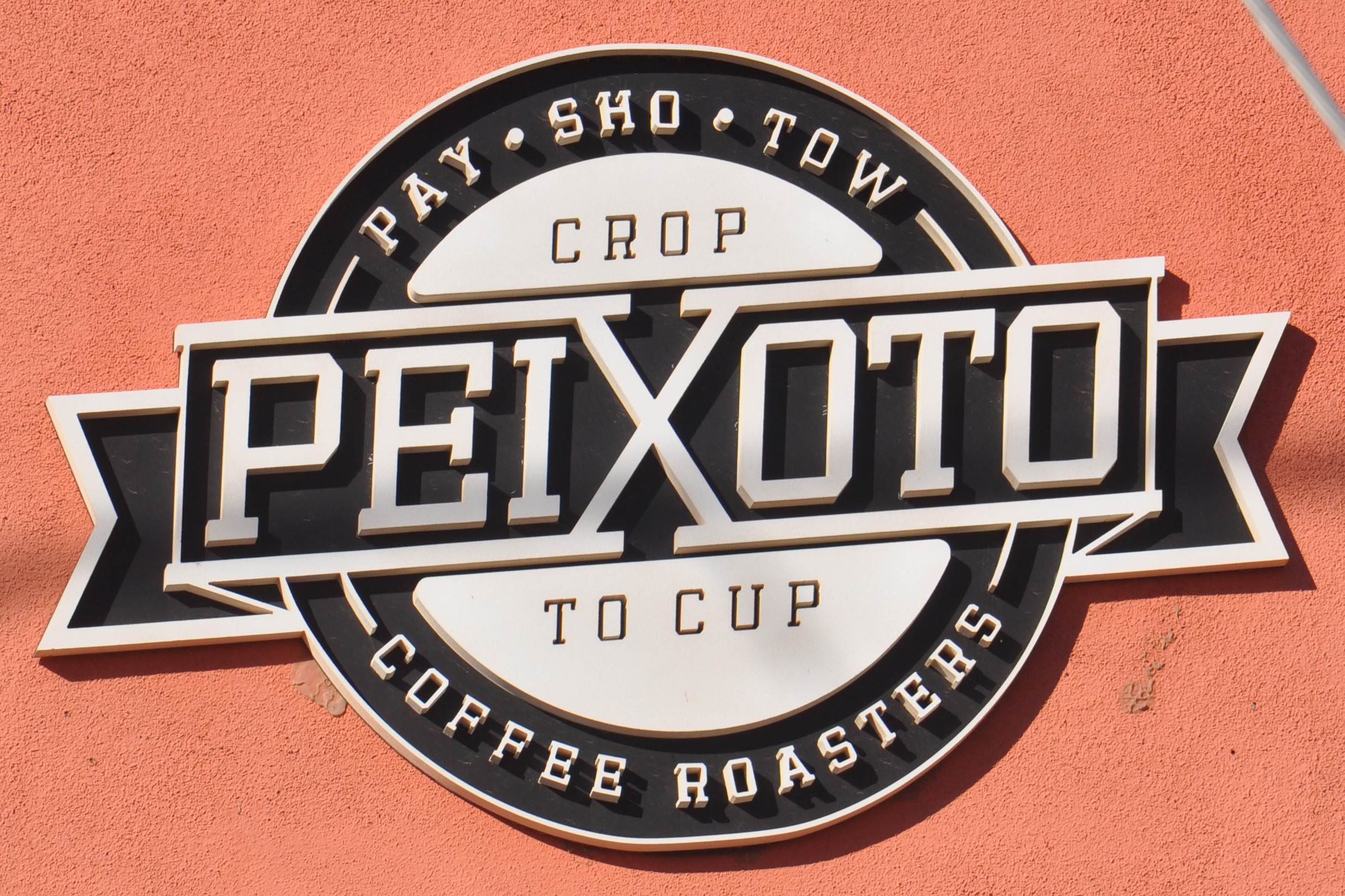 "The Peixoto logo from the wall outside, both esposing the crop to cup philosophy and explaining how to pronouce the name: ""Pay - Sho - Tow""."