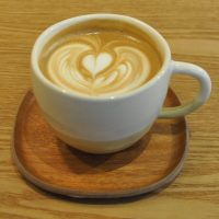 A creamy cappuccino, served in a white cup on a small wooden tray at Kurasu in Kyoto.