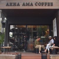 The front of Akha Ama Coffee La Fattoria in the heart of Chiang Mai, showing it's raised outdoor seating area.