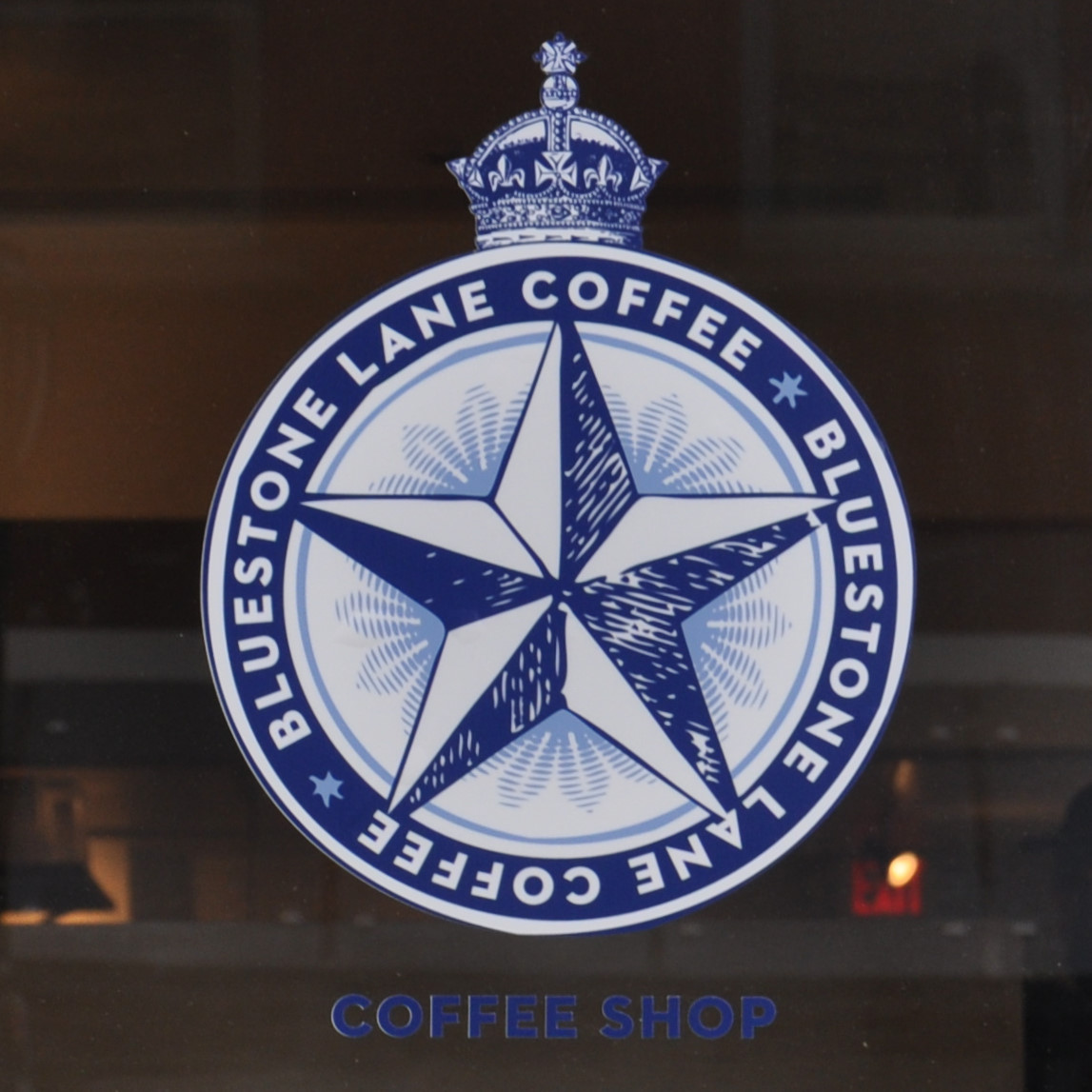 The Bluestone Lane logo (a five-pointed star in a blue circle) from the window of the cafe on Locust Street in Philadelphia.