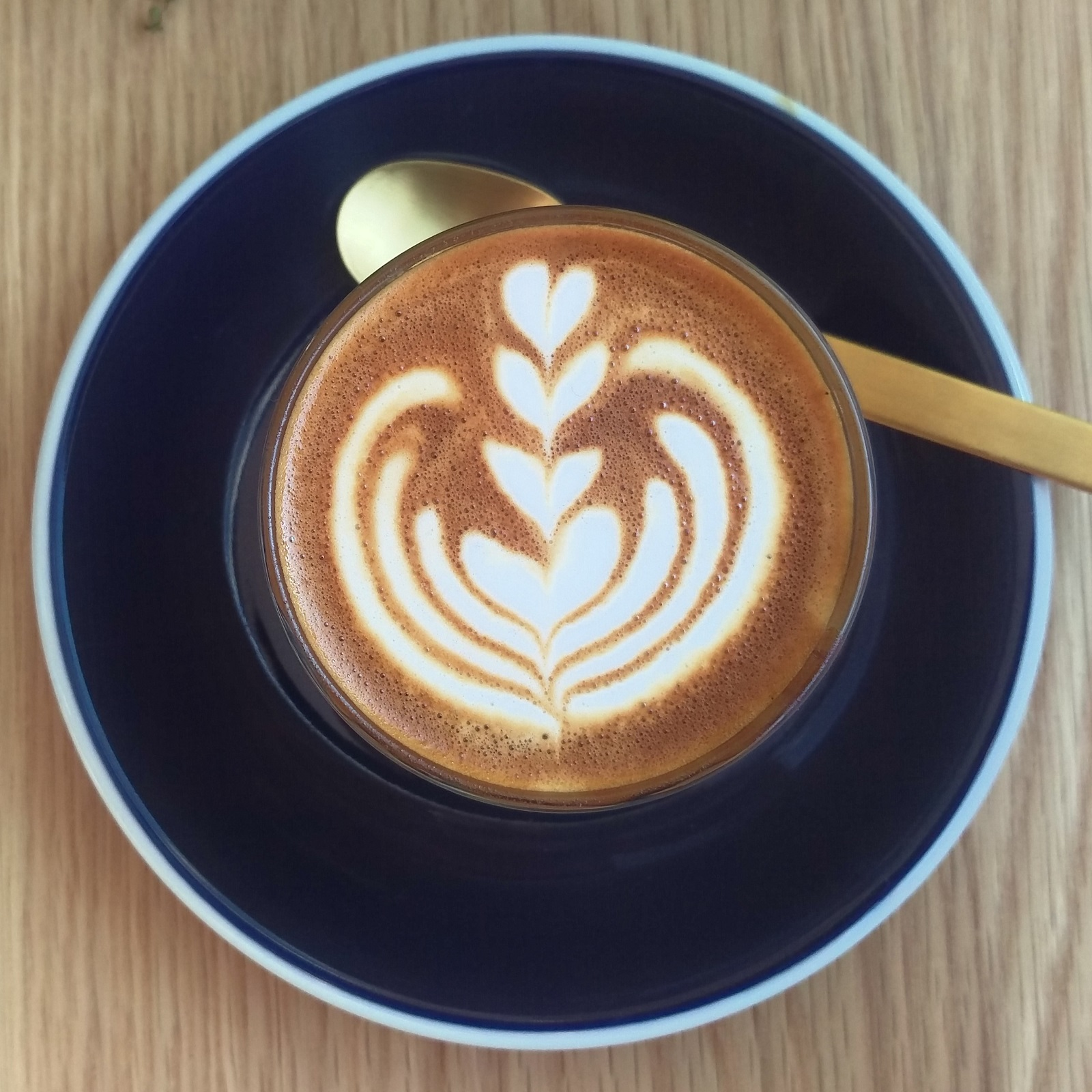 Some lovely latte art in an equally lovely piccolo made with the Party Blend at Party on Pavilion, London and served in a glass on a black saucer.