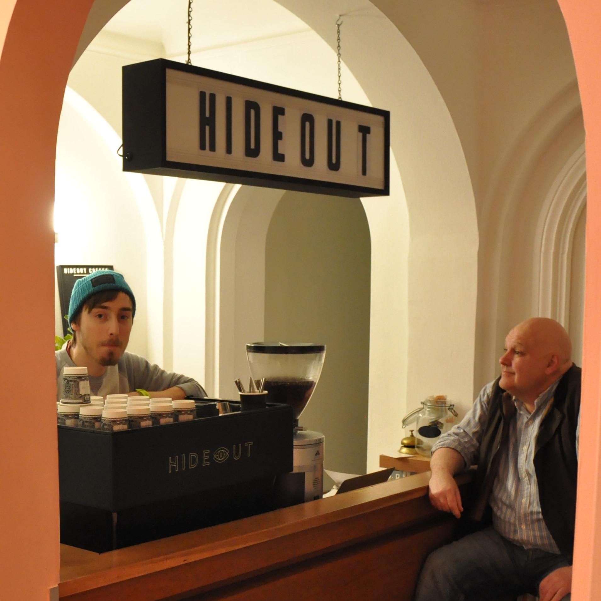 Head Barista, Jordan, talks with regular customer, David, at Hideout Coffee.