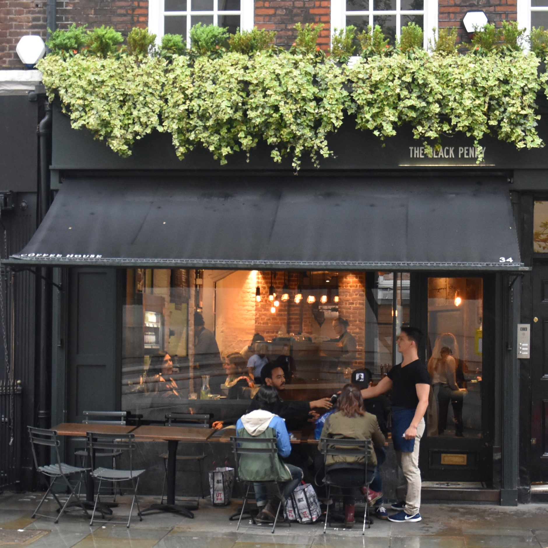 The front of The Black Penny on London's Great Queen Street, four small tables sheltering under the black awning.