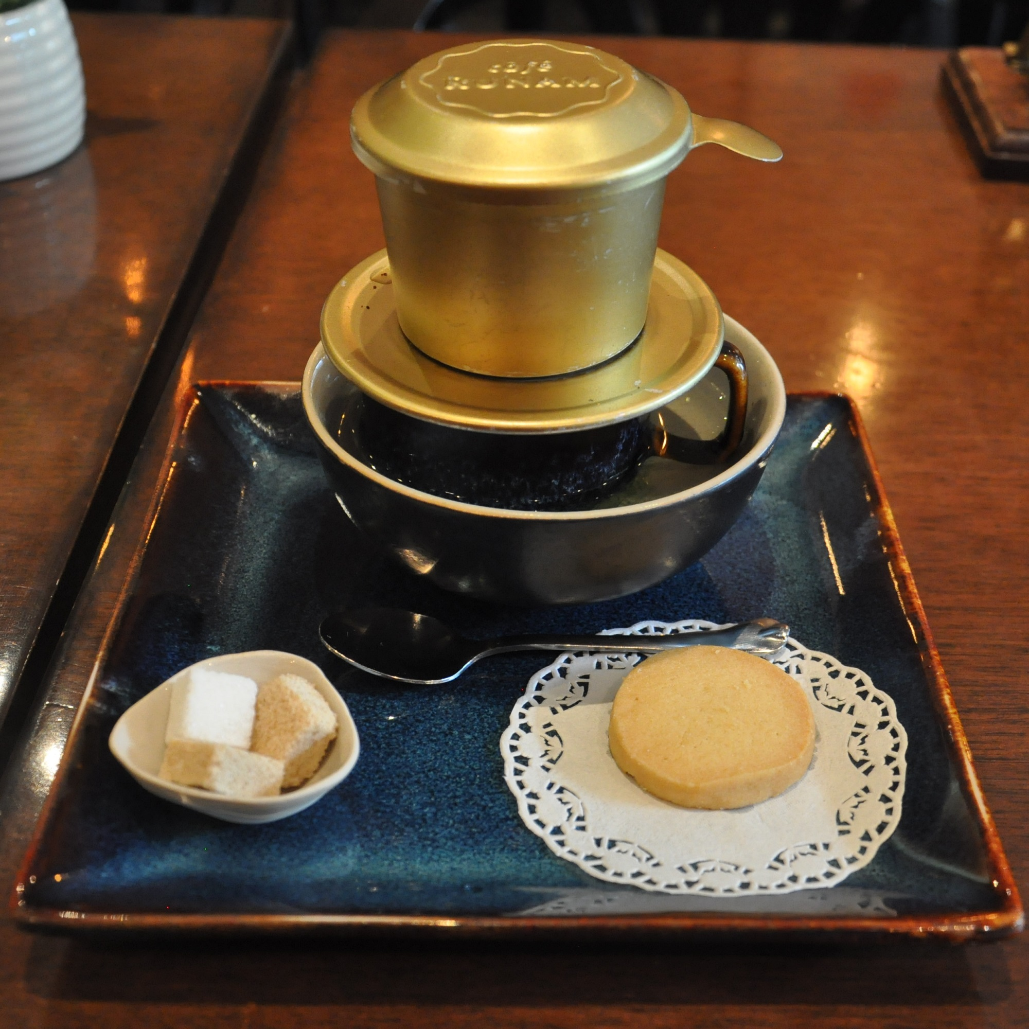 My coffee at RuNam Bistro in Hanoi, made with a traditional cup-top filter and beautifully-presented on a ceramic tray. Note the bowl of hot water the cup is standing in, which keeps the coffee warm.