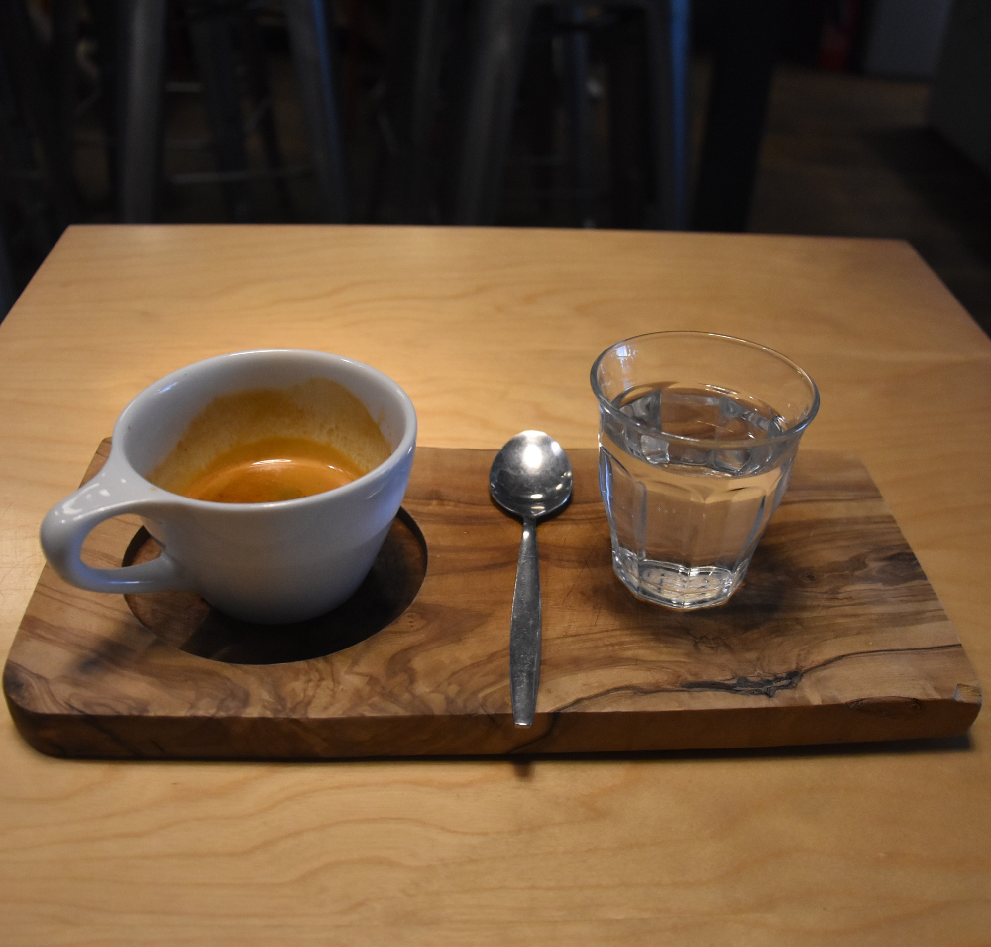 My single-origin Ethiopian Yirgacheffe, a washed coffee from the Negele Gorbitu co-operative, roasted and served by Beanberry Coffee in an over-sized cup on a wooden tray, a glass of water on the side.