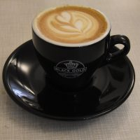 A flat white, served in a classic black cup, at Amsterdam's Black Gold.