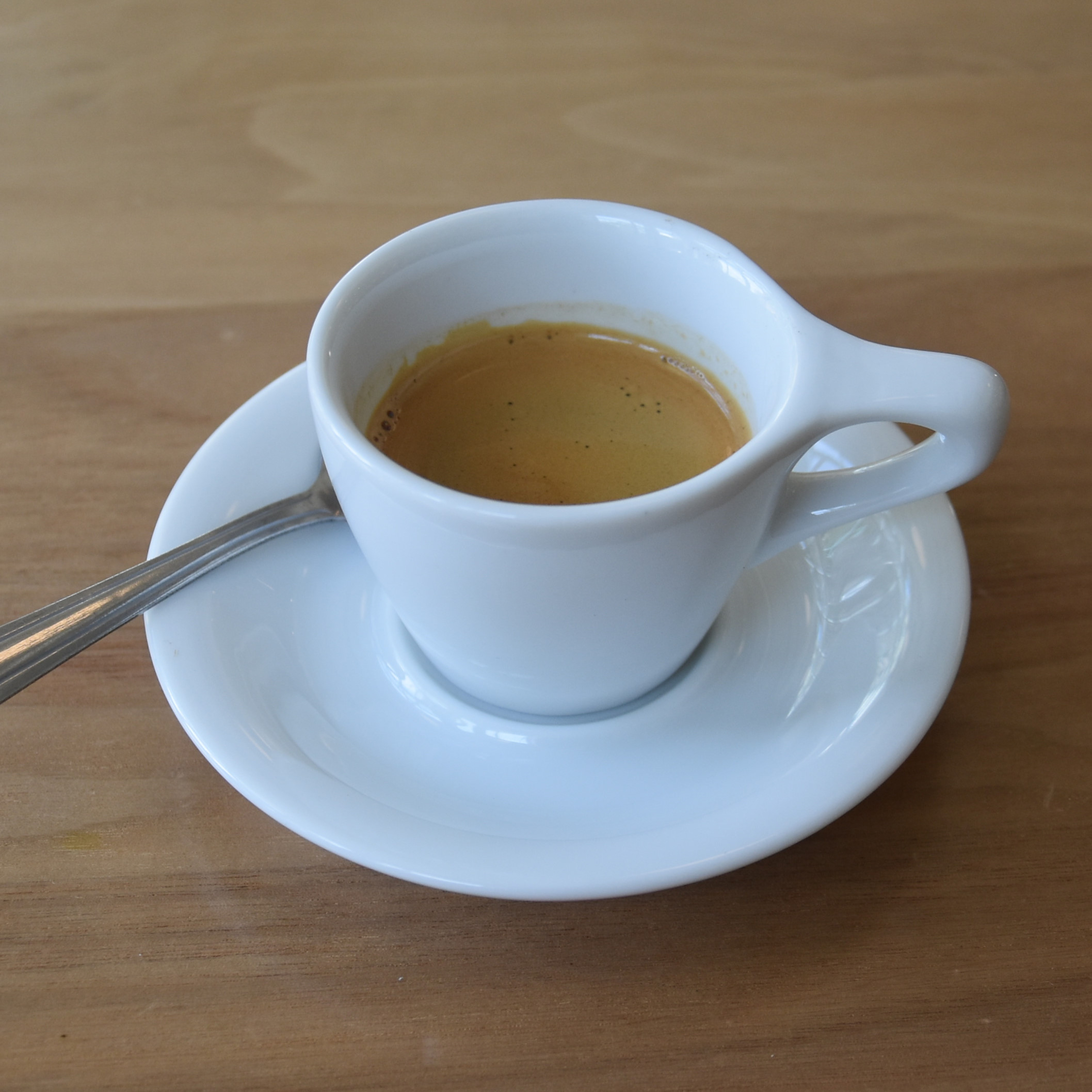 An organic Guatemalan Concepcion single-origin espresso from Kickapoo in Milwaukee, served in a classic white espresso cup with an oversized handle.