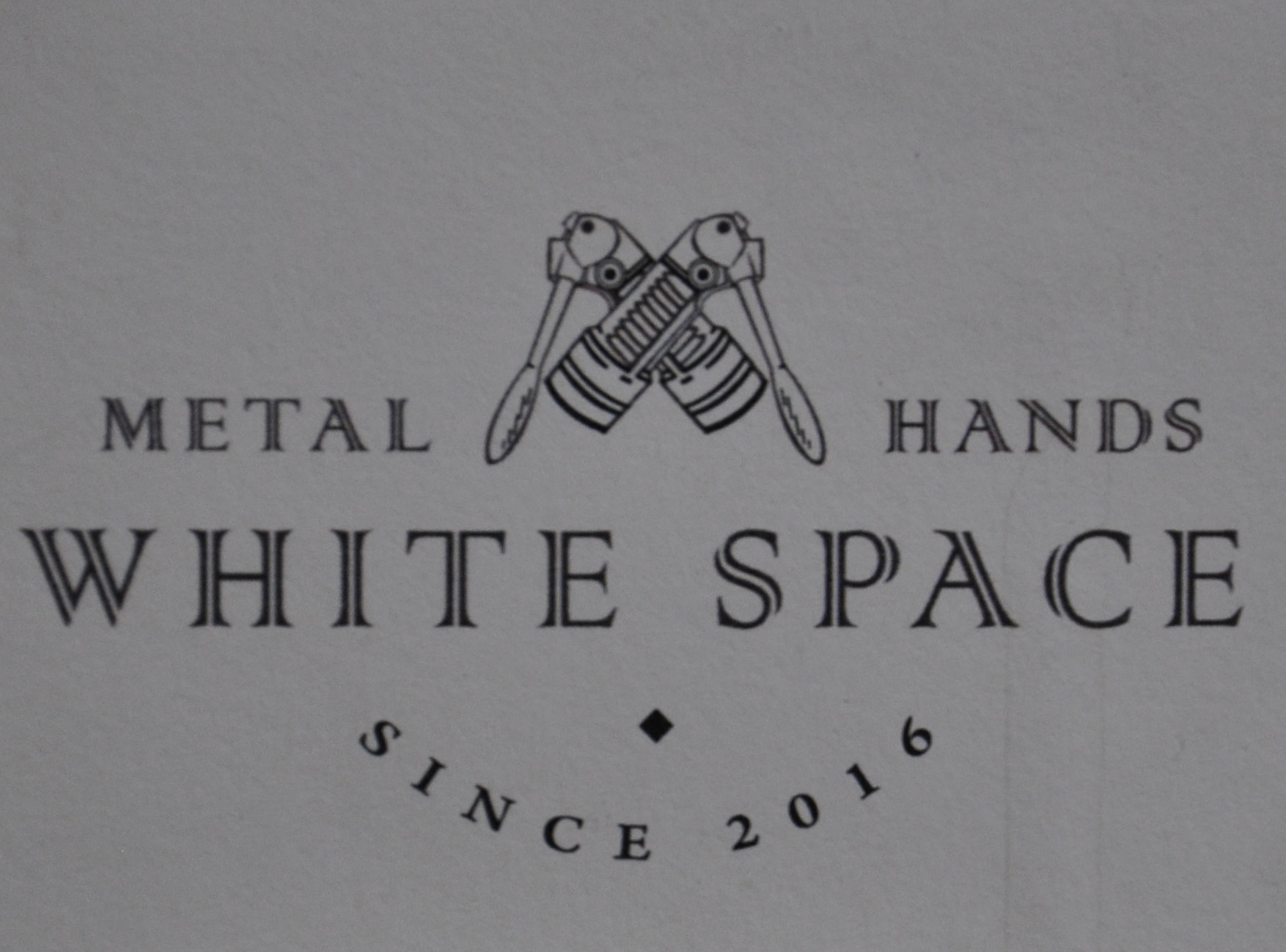 The logo of Metal Hands White Space from the menu,