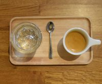 A lovely espresso, served on a wooden tray, with a glass of sparkling water on the side.