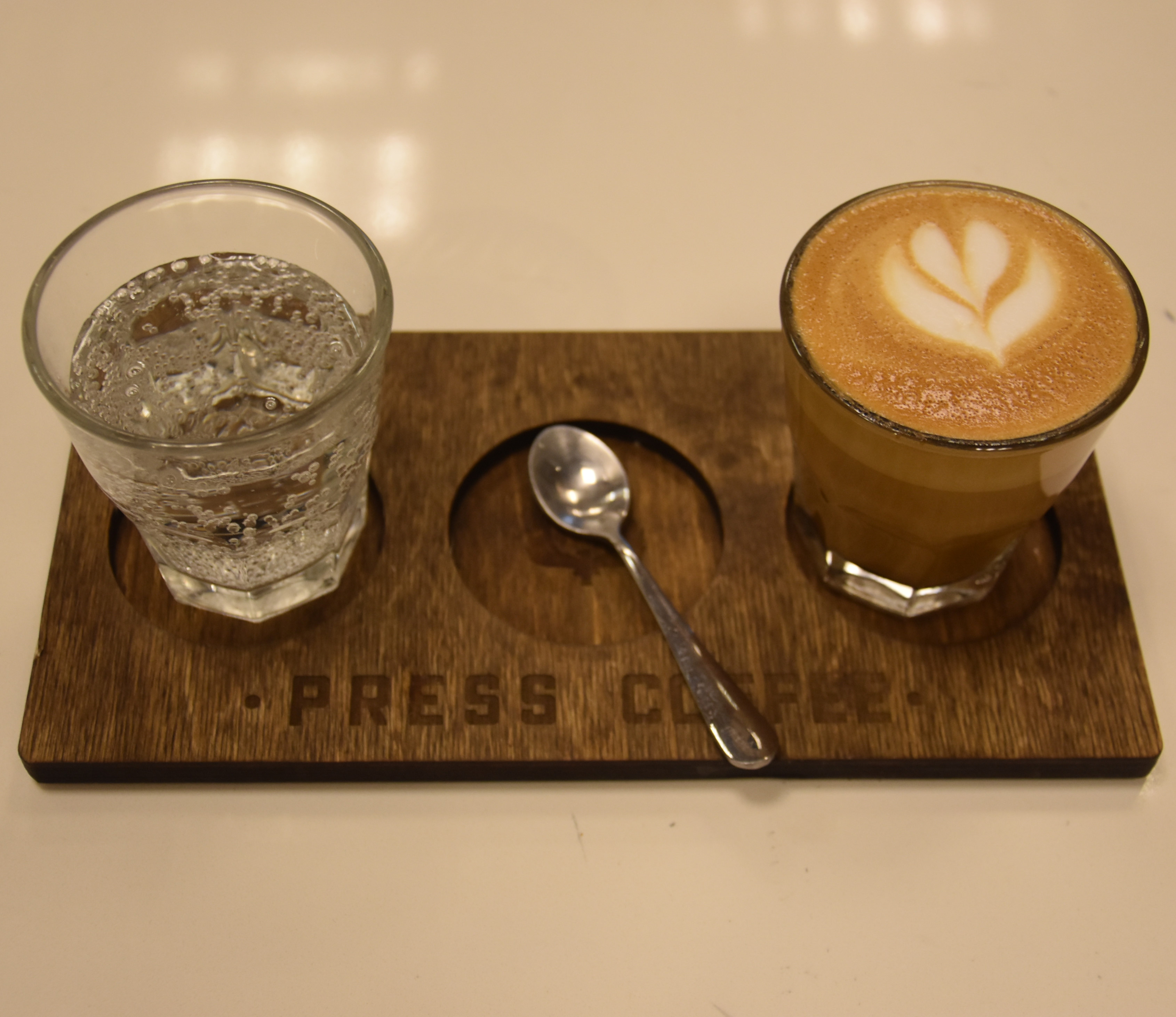My cortado at Press Coffee Waterfront, served on a wooden tray with a glass of sparkling water.