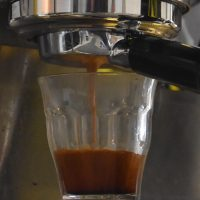 The single-origin Costa Rican espresso extracting into a glass from a bottomless portafilter on a Synesso espresso machine at Rival Bros Tasker Street location in Philadelphia.