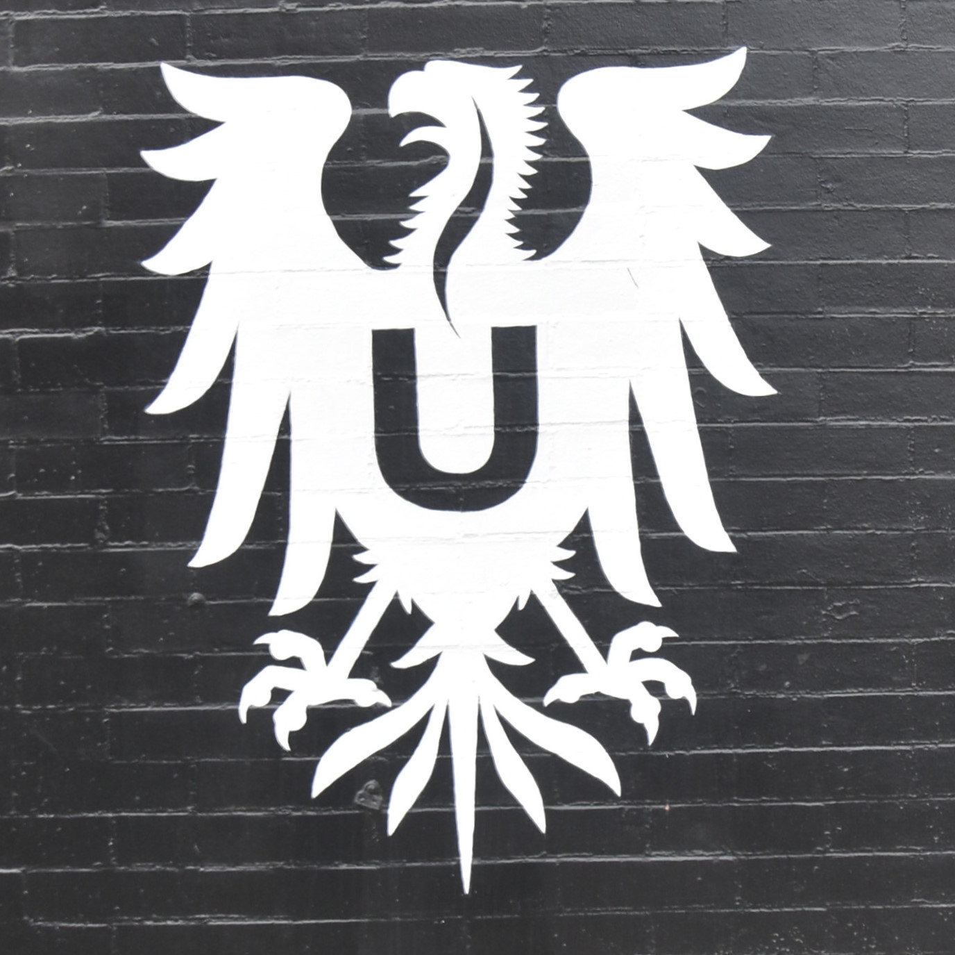 The Ultimo Coffee eagle, painted in white on the side of the Rittenhouse branch in Philadelphia.