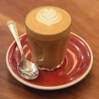 A piccolo in a glass on a red saucer at Cairngorm Coffee, Frederick Street, Edinburgh.