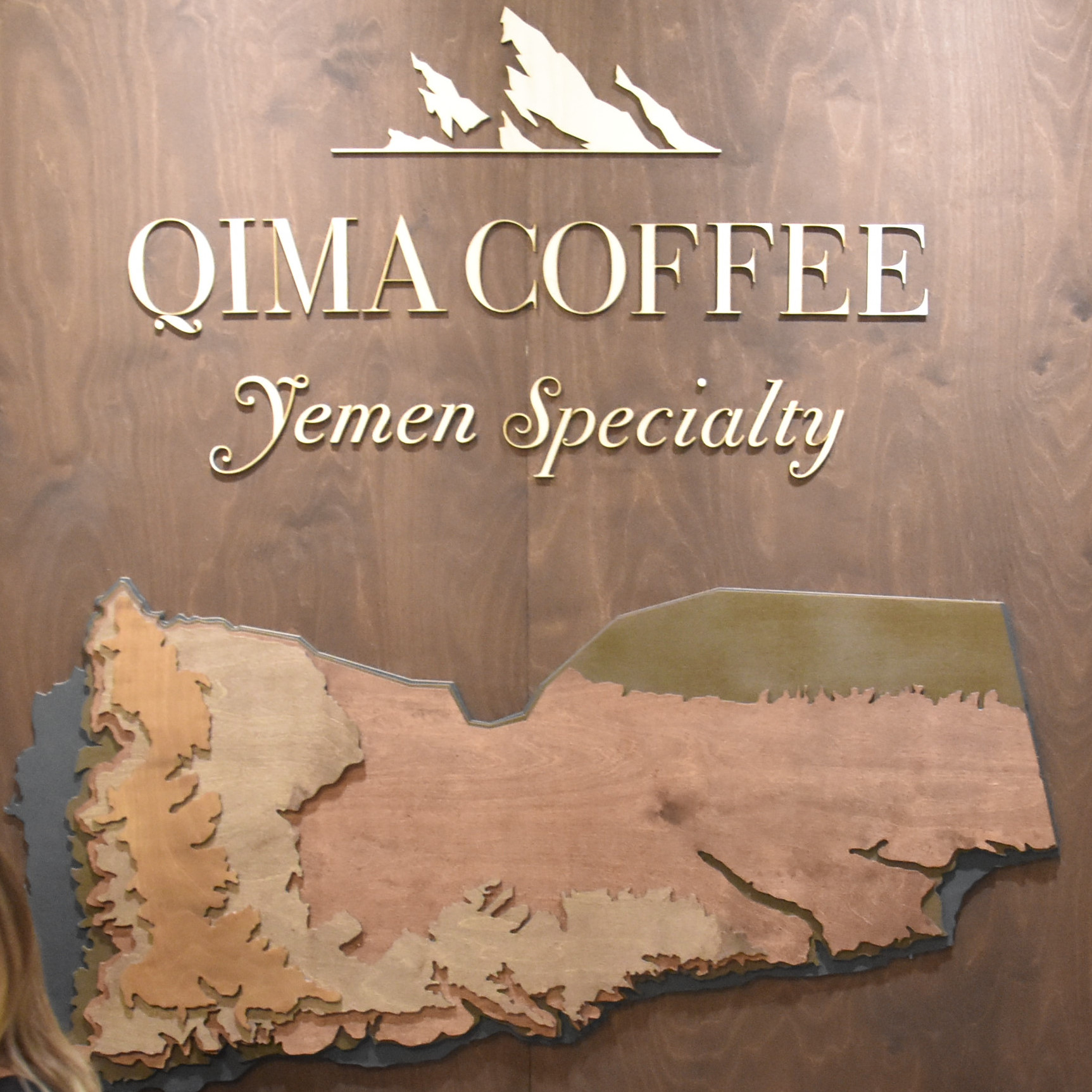 Detail from the stand of Qima Coffee, including a wooden relief map of Yemen, taken from the stand at the 2019 London Coffee Festival.