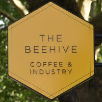 "The sign from outside The Beehive in Bethnal Green, with the slogan, ""Coffee & Industry""."