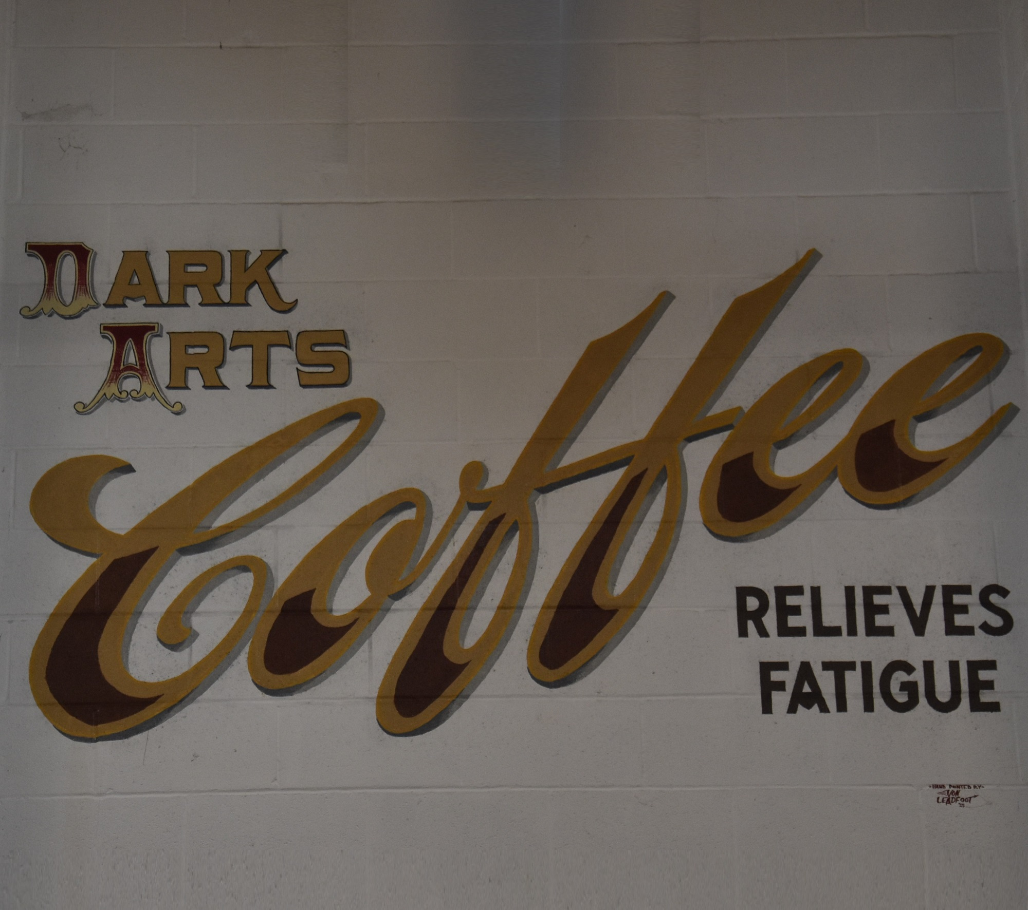 The logo from the back of the wall of I Will Kill Again, proudly proclaiming 'Dark Arts Coffee Relieves Fatigue'.