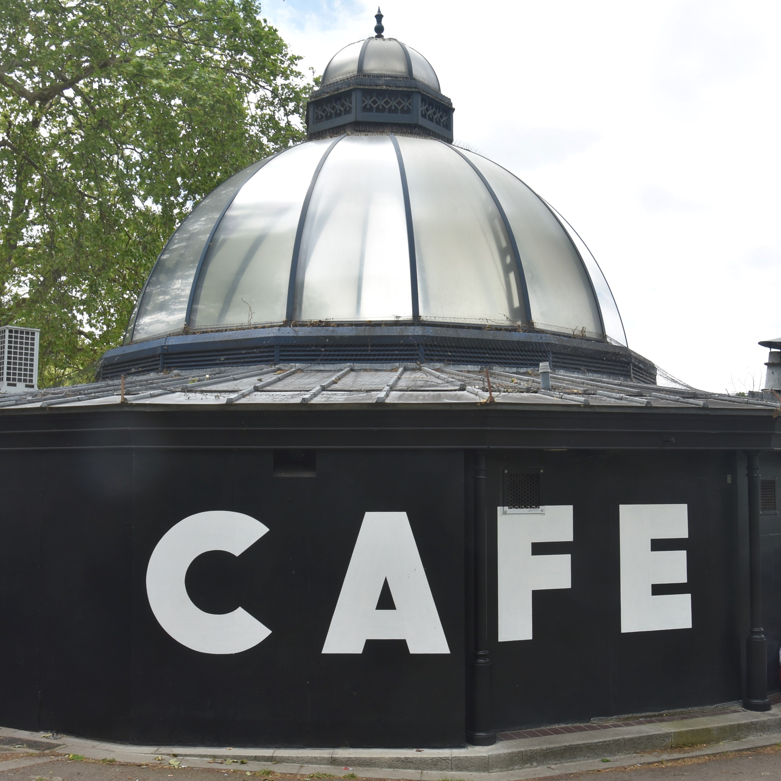 The word CAFE in white on the side wall of the Pavilion Cafe in Victoria Park, glass dome soaring above.