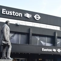 The bronze statue of Robert Louis Stephenson, who designed the original London and Birmingham Railway in the 19th Century, looking across to the modern London Euston station, built in the 1960s.