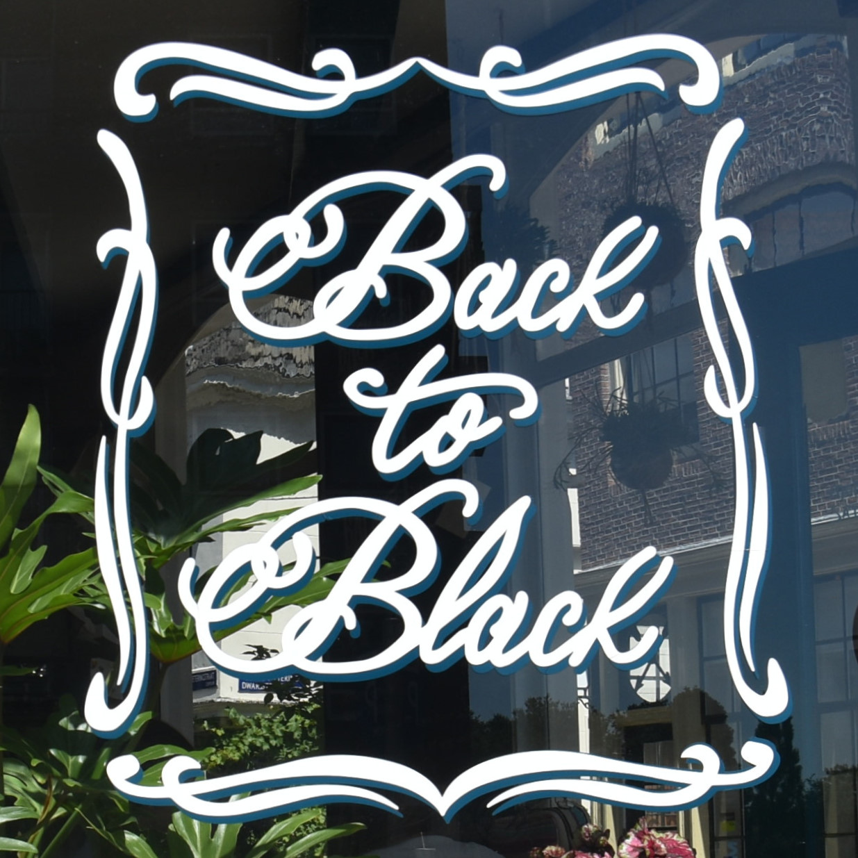 Details from the sign for Back to Black, written in a cursive script in the window of the coffee shop on Weteringstraat.