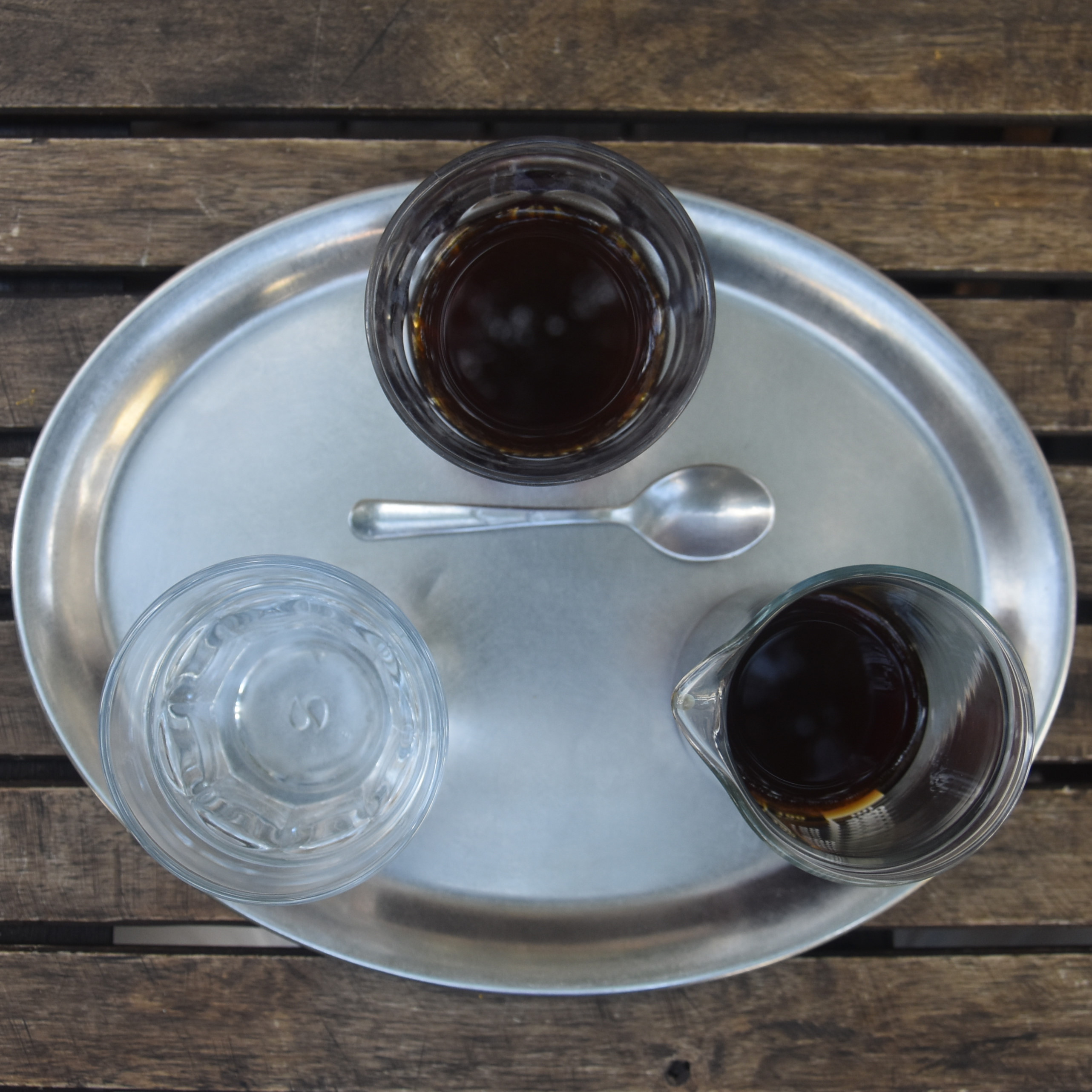 My pour-over, a natural Nicaraguan single-origin, presented in a carafe on an oval tray, along with a glass of water at Mamacoffee Londýnská in Prague.