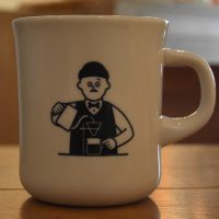 A cartoon figure of a man making a pour-over from the side of my mug at Foret Coffee, Nagano.