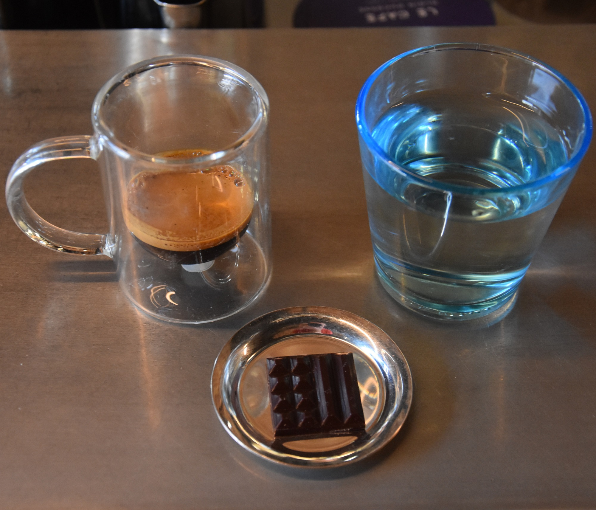 The signature espresso at Le Cafe Alain Ducasse in Coal Drops Yard, Kings Cross, served in a double-walled glass cup and a small square of chocolate.