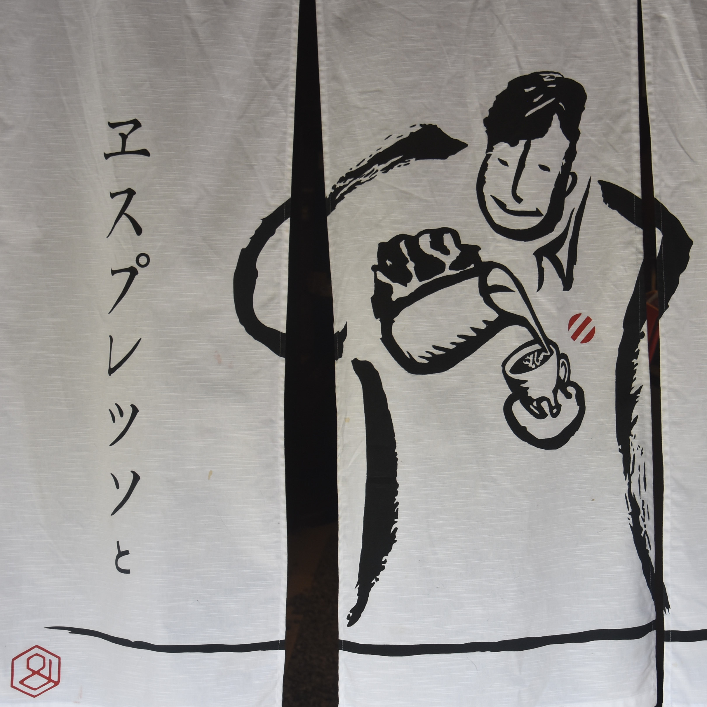 Details from the curtains hanging in the door of Bread, Espresso & Arashiyama Garden, Kyoto, showing a man pouring latte art.
