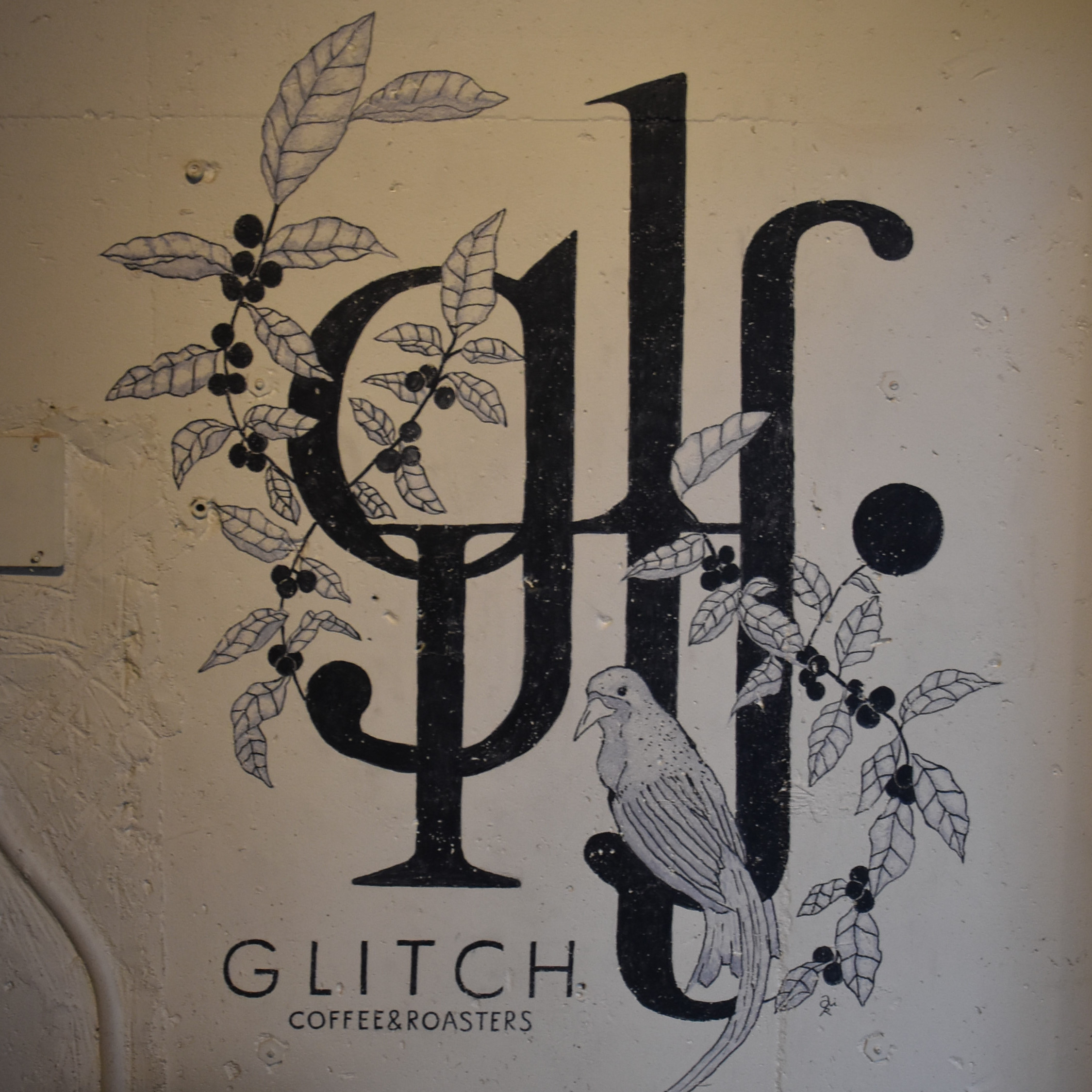 The Glitch Coffee & Roasters logo from the wall next to the roaster.