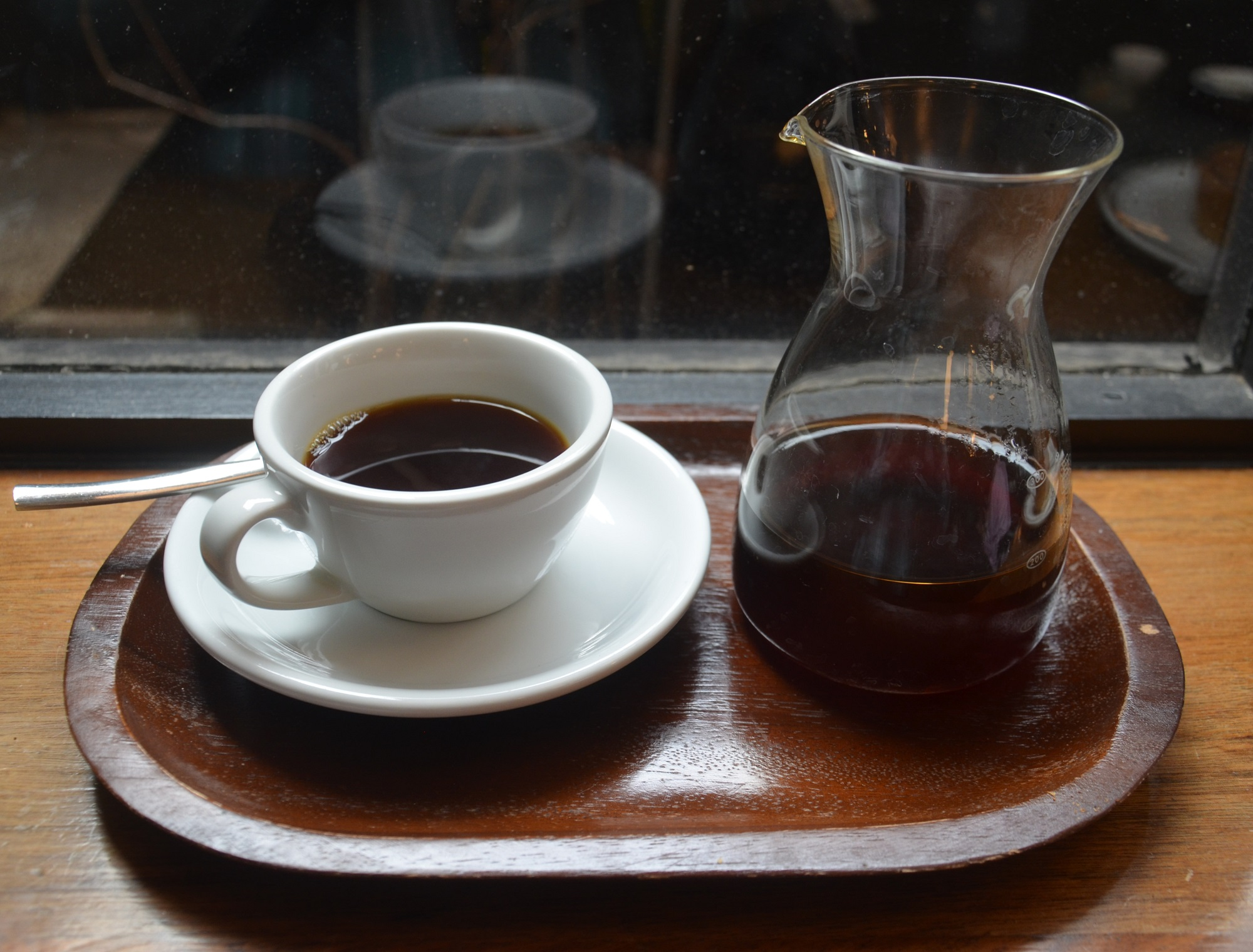 A V60 of the Galapagos San Cristolbol at HR Higgins, beautifully presented in a carafe, cup on one side, resting on the window-bar in the basement coffee room.