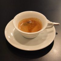 A single-origin espresso served in a wide-brimmed demitasse cup at Maruyama Single Origin in Aoyama, Tokyo, part of an espresso set where the same coffee is served in two different cups.