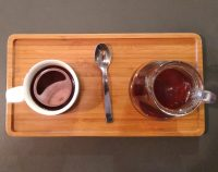 A V60 of a Gakui AA Kenyan single-origin served in a carafe, with the cup on one side, presented on a wooden tray at Coffeeangel TCD.