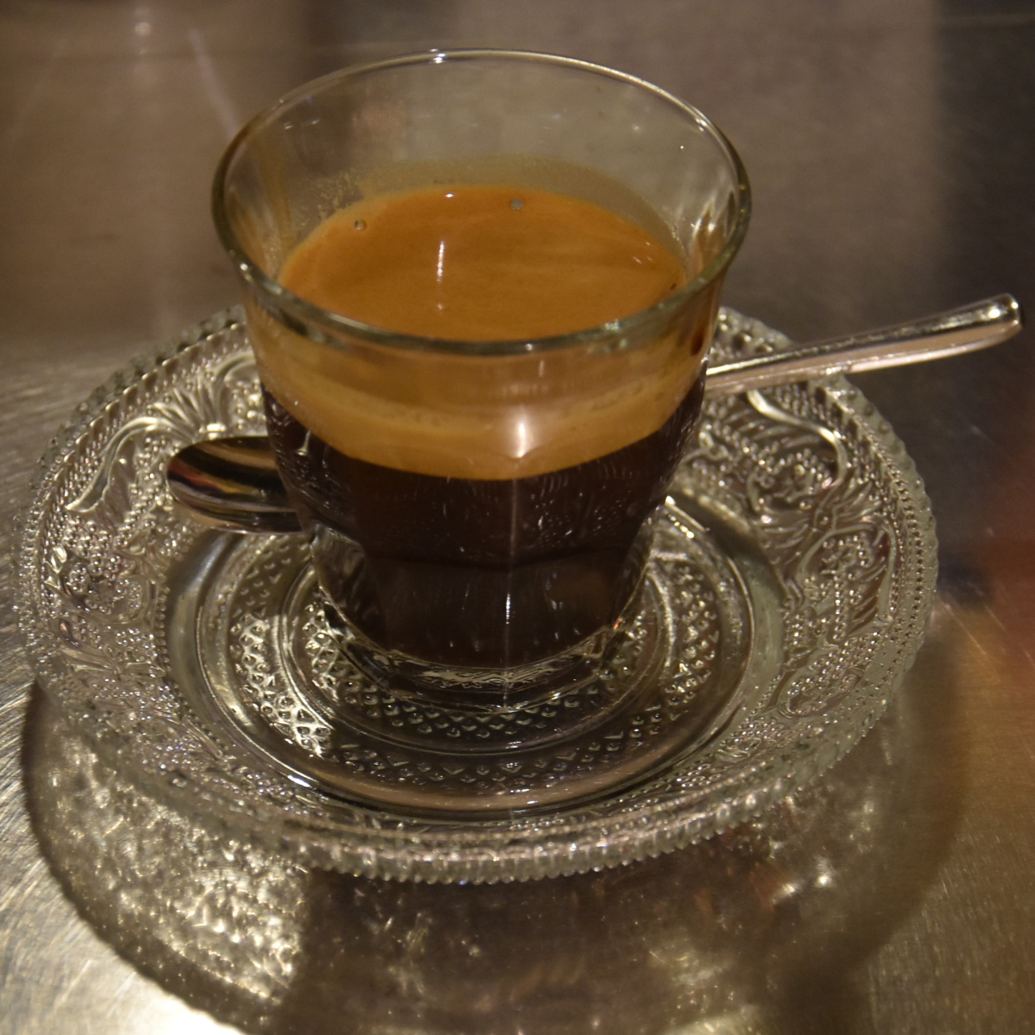 A lovely espresso, made with the house-blend at Blue Monday in Kanazawa and served in a glass, on a patterned glass saucer.