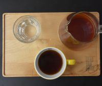 A V60 of a Kenyan single-origin served by Head Shot Coffee in a carafe on a wooden tray, with the cup of the side, along with a glass of water.